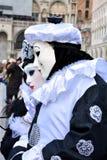 男人和女服皮埃罗华丽服装一对未认出的夫妇与黑白贝雷帽的在威尼斯狂欢节期间 免版税库存照片