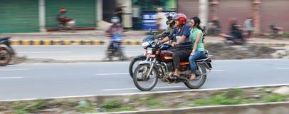 男人和妇女一辆摩托车的在加德满都,尼泊尔 免版税库存照片