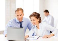 男人和妇女与膝上型计算机一起使用在办公室 库存图片