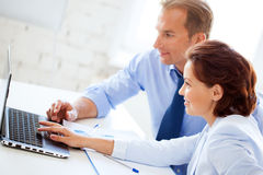男人和妇女与膝上型计算机一起使用在办公室 免版税图库摄影