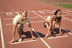 男人和妇女低开始状态流动的表面体育场 连续竞争或性别种族 更加快速的运动员达到 免版税库存照片