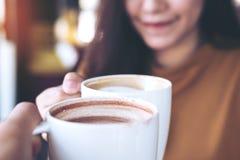 男人和妇女使在咖啡馆的咖啡杯叮当响 库存照片