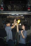 男人和妇女修理一辆残破的汽车 免版税库存图片