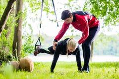 男人和妇女做俯卧撑的健身训练的 免版税库存照片