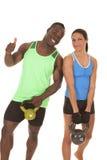 男人和妇女健身她的更多重量 免版税库存照片