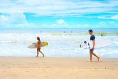 男人和妇女冲浪的海滩 库存照片