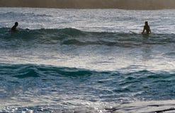 男人和妇女冲浪 免版税图库摄影