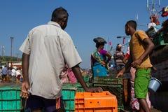 男人和妇女准备卸载捕鱼船 一个小捕鱼港口在南印度 印度,卡纳塔克邦, 2017年 免版税库存照片