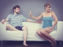 男人和妇女分歧的坐沙发 免版税库存照片