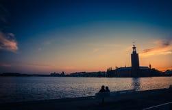 男人和妇女剪影坐长凳在散步看斯德哥尔摩政府大厦Stadshuset的湖梅拉伦湖码头银行 免版税库存图片
