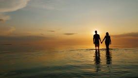 男人和妇女努力去做海在日落,握手 股票录像