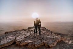 男人和妇女单独年轻夫妇有背包的在以色列Neqev沙漠敬佩日出看法  免版税库存图片