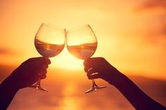 男人和妇女叮当响的酒杯用在日落的香槟 库存照片