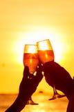 男人和妇女叮当响的酒杯用在日落的香槟 免版税库存图片