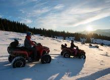 男人和妇女四轮汽车的ATV在雪骑自行车,享受日落在山在冬天 免版税库存图片