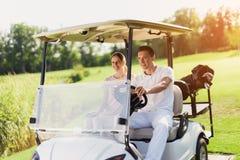 男人和妇女在一辆白色高尔夫车坐 在汽车的后车箱与高尔夫俱乐部的一个袋子 图库摄影