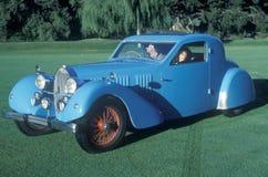 男人和妇女在一辆蓝色Bugatti汽车坐在葡萄酒车展在Pebble海滩,加利福尼亚,加州 1985年 库存图片