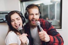 男人和妇女在一间现代录音室唱一首歌曲 库存照片