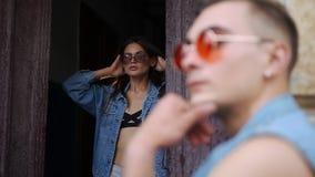 男人和妇女在与太阳镜的偶然街道样式穿戴了在一个老门前摆在外面在街道上 股票录像