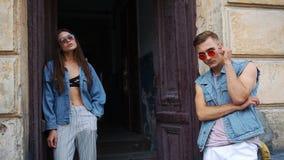 男人和妇女在与太阳镜的偶然街道样式穿戴了在一个老门前摆在外面在街道上 影视素材