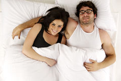 男人和妇女在注视着照相机微笑的白色床上放置了 免版税库存图片
