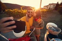 男人和妇女在浪漫旅途上在滑行车在日落和采取selfie 免版税库存照片