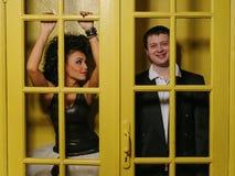 男人和妇女在老门后 免版税库存照片