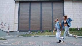 男人和妇女在街道上跑的偶然街道样式穿戴了 股票视频