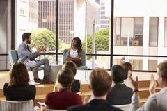 男人和妇女在观众前面谈话在企业研讨会 库存照片