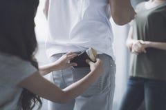 男人和妇女在那边人后站立并且谈话,是从人后面口袋拔出钱包的女孩 库存图片