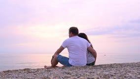 男人和妇女坐海海滩在日落 股票录像