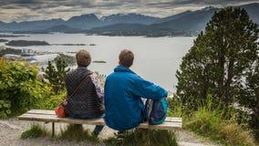 男人和妇女坐长凳并且看挪威全景 旅游业题材  免版税图库摄影