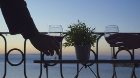 男人和妇女坐阳台和饮用的红葡萄酒在海的背景 特写镜头 股票录像