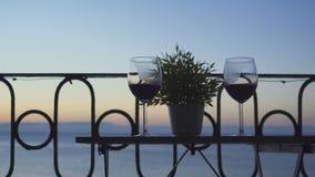 男人和妇女坐阳台和饮用的红葡萄酒在海的背景 特写镜头 股票视频