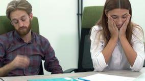 男人和妇女工作在坐直在桌关闭的现代办公室 人们困和疲乏 股票录像
