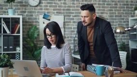男人和妇女工友与谈话的膝上型计算机一起使用分享企业想法 影视素材