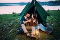 男人和妇女帐篷的拿着一个手电 免版税库存图片