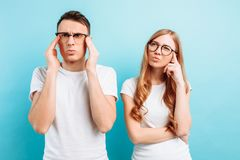 男人和妇女戴眼镜,被聚焦和沉思,在浅兰的背景 免版税库存图片