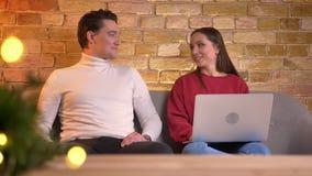 男人和妇女投入他们的膝上型计算机,并且智能手机坐更加接近并且起动愉快地沟通在舒适家庭环境 股票录像