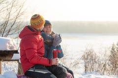 男人和妇女投掷雪和获得乐趣户外以河为目的 冷淡的晴朗的冬日 库存照片