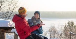 男人和妇女投掷雪和获得乐趣户外以河为目的 冷淡的晴朗的冬日 免版税库存图片