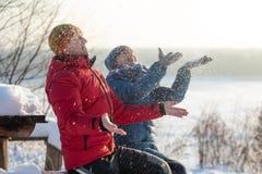 男人和妇女投掷雪和获得乐趣户外以河为目的 冷淡的晴朗的冬日 免版税图库摄影