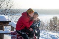 男人和妇女投掷雪和获得乐趣户外以河为目的 冷淡的晴朗的冬日 图库摄影