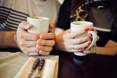 男人和妇女拿着一个杯子在咖啡馆的咖啡 免版税库存图片