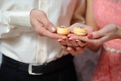 男人和妇女拿着他们的在蛋白杏仁饼干的圆环 免版税库存照片