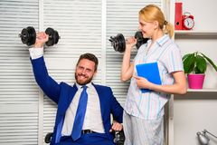 男人和妇女提高重的哑铃  好工作概念 上司 免版税图库摄影