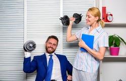 男人和妇女提高重的哑铃 强的强有力的经营战略 好工作概念 上司商人和办公室 库存图片