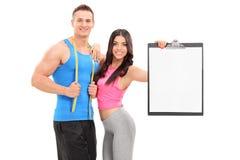 男人和妇女摆在与剪贴板的运动服的 免版税库存图片