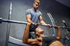 男人和妇女有屈曲肌肉在健身房的杠铃的 库存照片