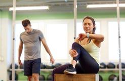 男人和妇女有心率跟踪仪的健身房的 免版税库存照片